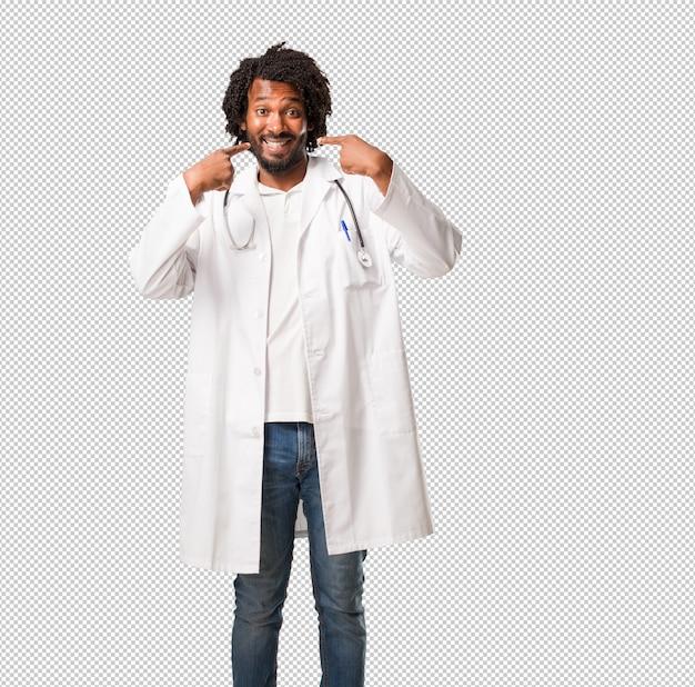 Красивый афро-американский врач улыбается, указывая на рот, концепция идеальных зубов, белые зубы, имеет веселое и веселое отношение