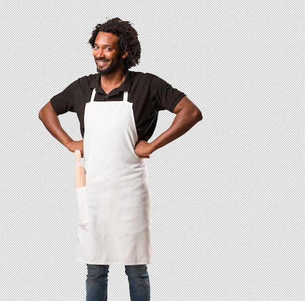 ハンサムなアフリカ系アメリカ人のパン屋の腰に手、立って、リラックスして笑顔、非常に肯定的で陽気な