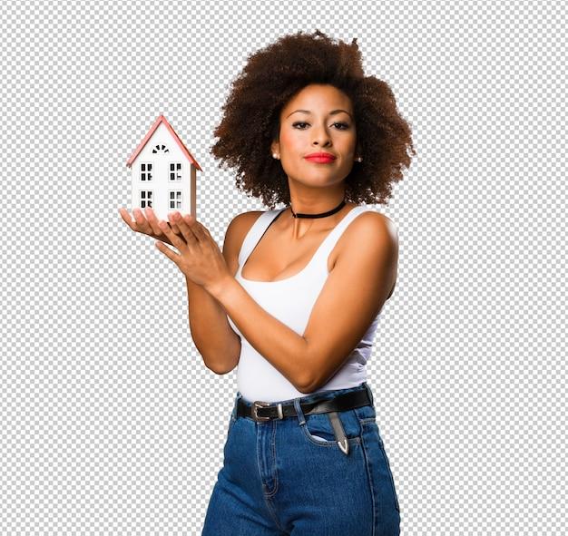 小さな家を保持している若い黒人女性