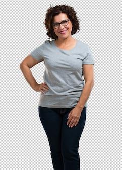 Женщина средних лет с руками на бедрах, стоя, расслабленная и улыбающаяся, очень позитивная и веселая