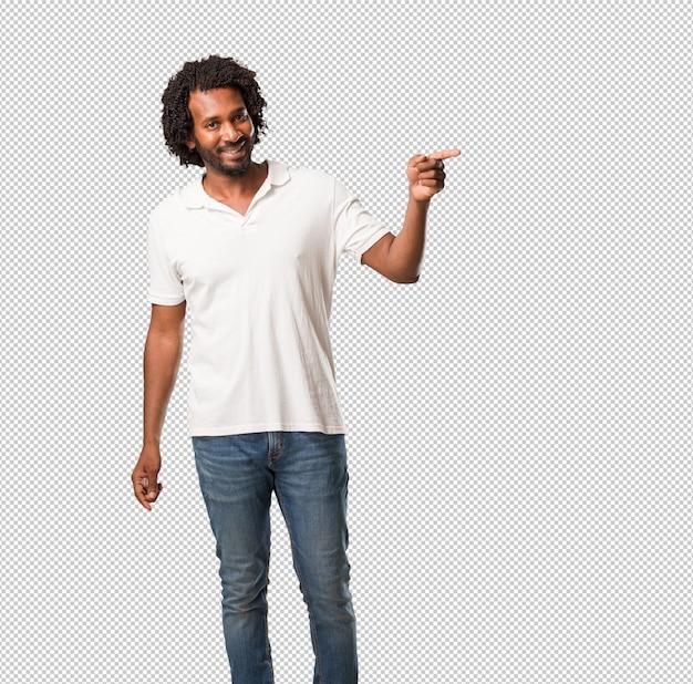 ハンサムなアフリカ系アメリカ人は、自然でカジュアルな何かを提示して驚いて笑みを浮かべて、側を指しています