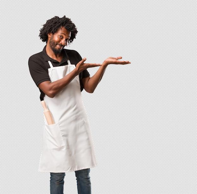 ハンサムなアフリカ系アメリカ人のパン屋は何かを手で押し、製品を見せ、笑顔で陽気、想像上のオブジェクトを提供しています