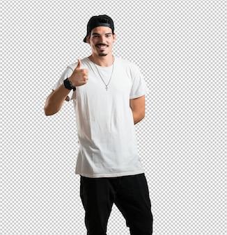 Молодой рэпер мужчина веселый и возбужденный, улыбается и поднимает палец вверх, успех и одобрение, ок жест