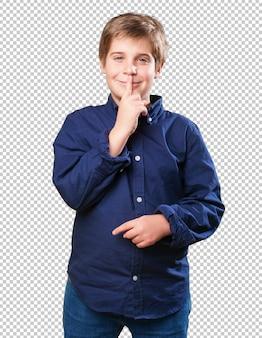 沈黙のジェスチャーをしている男の子