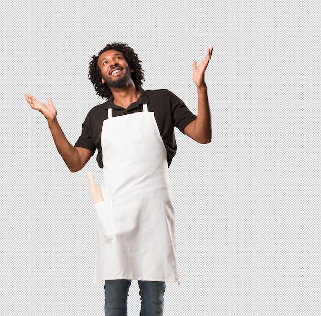 ハンサムなアフリカ系アメリカ人のパン屋は笑って楽しんで、リラックスして陽気で、自信と成功を感じています