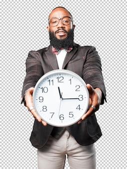 Деловой черный человек держит большие часы