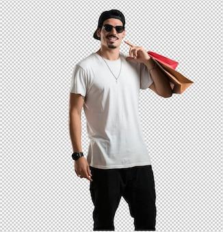 陽気な若い笑顔の男、買い物袋を運んで非常に興奮して、買い物に行く準備ができて、新しいオファーを探す