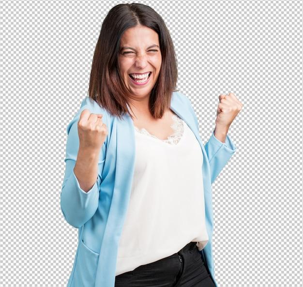 中年の女性は非常に幸せで興奮し、腕を上げ、勝利または成功を祝い、宝くじに当選しました