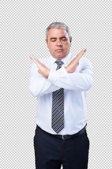 腕でクロスをしている中年の男性