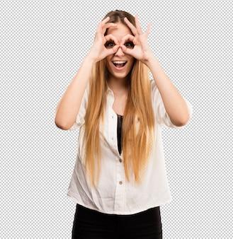 メガネのジェスチャーをしているかなり若い女性