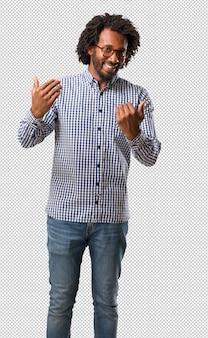 Красивый бизнес афроамериканец мужчина приглашает прийти, уверенно и улыбается, делая жест рукой, будучи позитивным и дружелюбным
