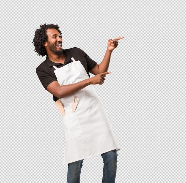 ハンサムなアフリカ系アメリカ人のパン、側を指して、驚いた笑みを浮かべて、自然でカジュアルな何かを提示