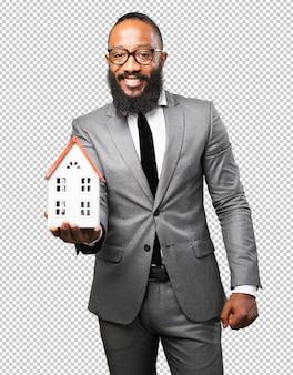 Бизнес черный человек, держащий дом