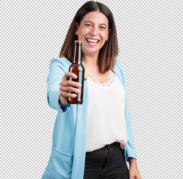 Женщина средних лет счастлива и весела, держит бутылку пива, чувствует себя хорошо после напряженного рабочего дня, готова смотреть футбольный матч по телевизору