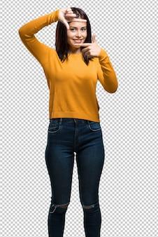 カメラのように焦点を合わせようとして、手でフレームの形を作る若いきれいな女性