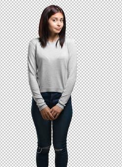 優柔不断と不安の肩を疑って肩をすくめて、何かについて不確かな若いきれいな女性