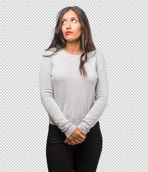 疑問や混乱、アイデアを考えたり、何かを心配している若いインド人女性の肖像画