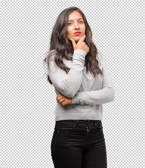 考えて見上げて、アイデアについて混乱している若いインド人女性の肖像画は、解決策を見つけようとしている