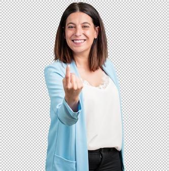 Женщина средних лет приглашает прийти, уверенная в себе и улыбающаяся, делающая жест рукой, позитивная и дружелюбная