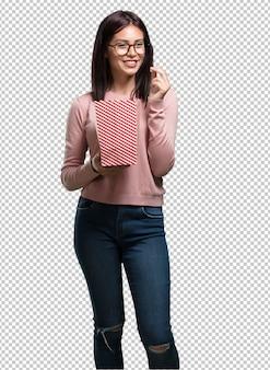 Молодая красавица счастлива и очарована, держит в руках полосатое ведерко для попкорна, удивлена новым фильмом, глаза открыты и выражение восхищения