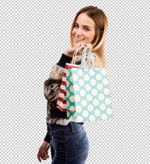 Милая молодая женщина держа хозяйственные сумки