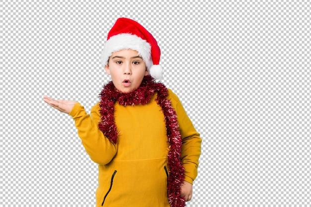 分離されたサンタ帽子をかぶってクリスマスの日を祝う少年は、手のひらにコピースペースを保持しています。