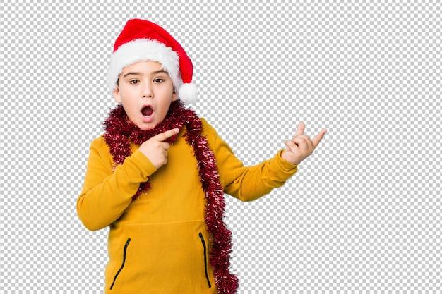 分離されたサンタ帽子をかぶってクリスマスの日を祝う少年は、手のひらにコピースペースを保持して興奮しています。