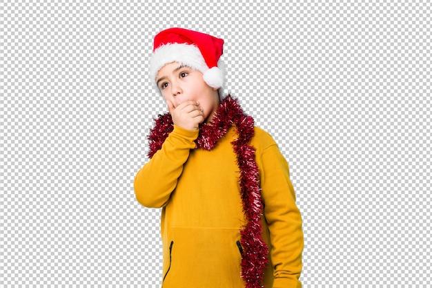 サンタの帽子をかぶってクリスマスの日を祝う少年は、手で口を覆っているコピースペースに思慮深い探しています。