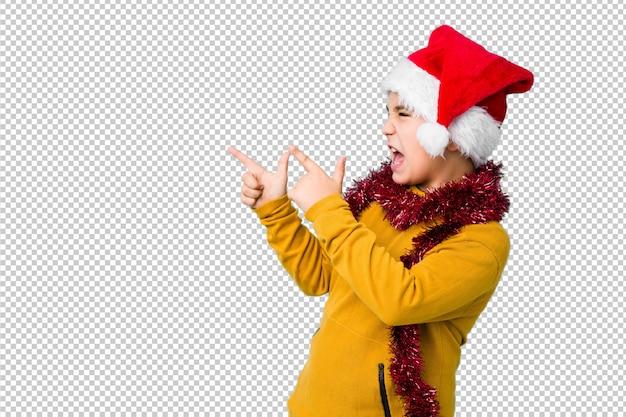 クリスマスの日を祝うサンタ帽子をかぶった少年は、コピースペースに人差し指で指し、興奮と欲望を表現します。
