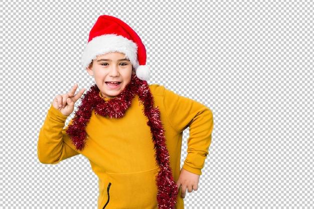 サンタの帽子をかぶってクリスマスの日を祝う少年は、勝利のサインを示し、広く笑顔を分離しました。