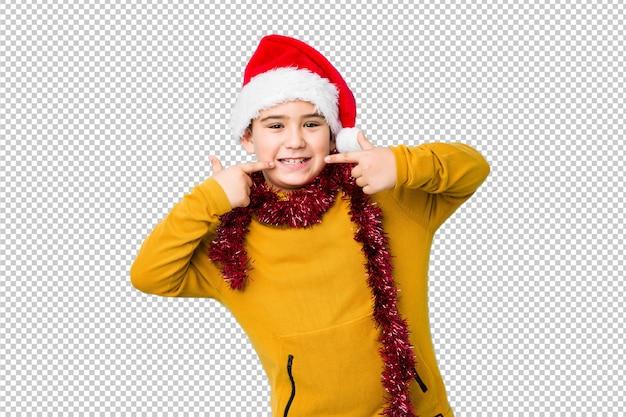サンタの帽子をかぶってクリスマスの日を祝う少年は笑顔を分離し、口に指を指しています。