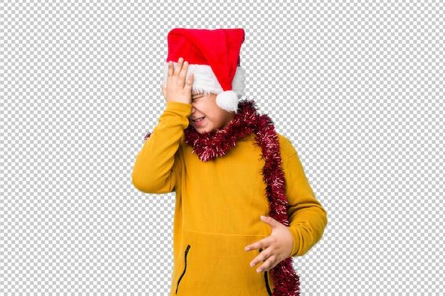 サンタの帽子をかぶってクリスマスの日を祝う少年は、何かを忘れて、額を手のひらでたたいて目を閉じます。