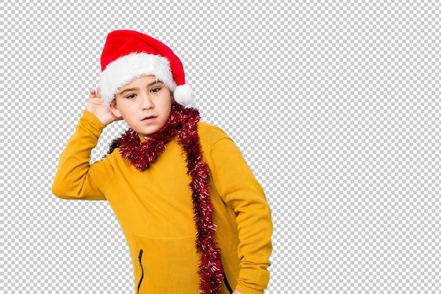 ゴシップを聞いてしようとして分離されたサンタ帽子をかぶってクリスマスの日を祝う少年。