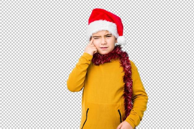 サンタ帽子をかぶっているクリスマスの日を祝っている小さな男の子は、人差し指で失望のジェスチャーを示します。