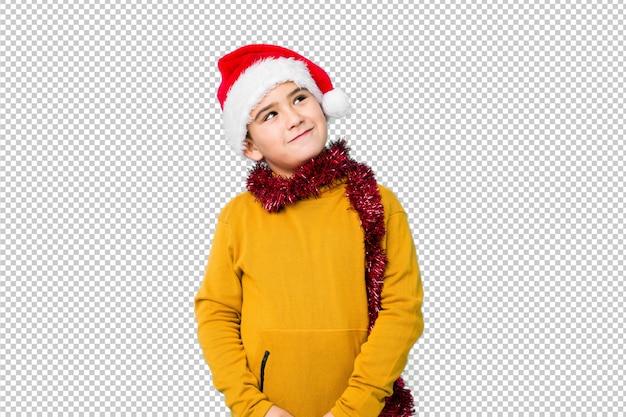 サンタの帽子をかぶってクリスマスの日を祝う小さな男の子は、目標と目的を達成することを夢見て