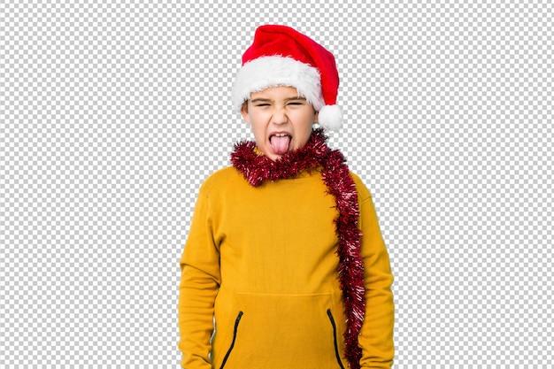 サンタの帽子をかぶってクリスマスの日を祝う少年は、舌を突き出して面白いとフレンドリーな分離しました。
