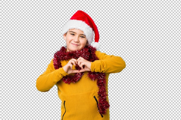 サンタの帽子をかぶってクリスマスの日を祝う少年は笑みを浮かべて、手でハートの形を示します。
