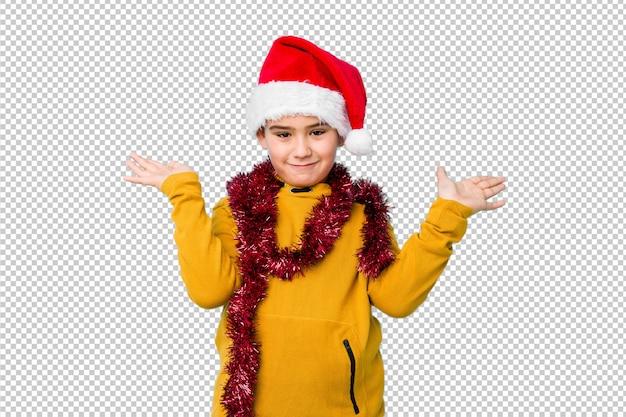 サンタの帽子をかぶってクリスマスの日を祝う少年は腕でスケールを作り、幸せと自信を感じます。