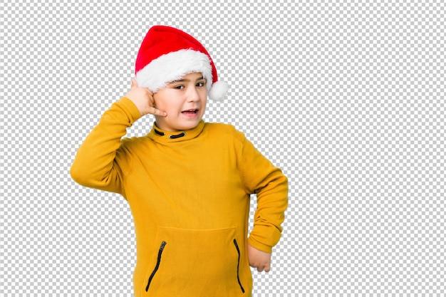 指で携帯電話の通話ジェスチャーを示すサンタ帽子をかぶってクリスマスの日を祝う少年。