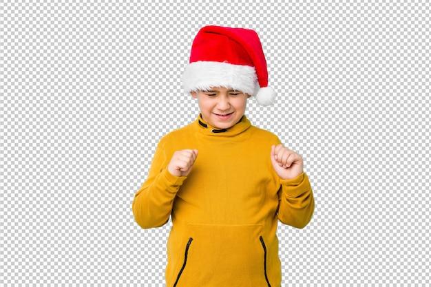 幸せな成功を感じて、拳を上げるサンタ帽子をかぶってクリスマスの日を祝う少年。勝利のコンセプト。