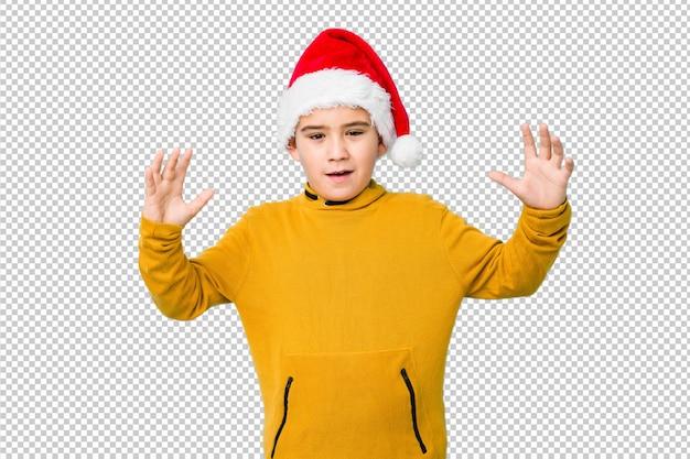 楽しい驚きを受けて、興奮して、手を上げるサンタ帽子をかぶってクリスマスを祝う少年。