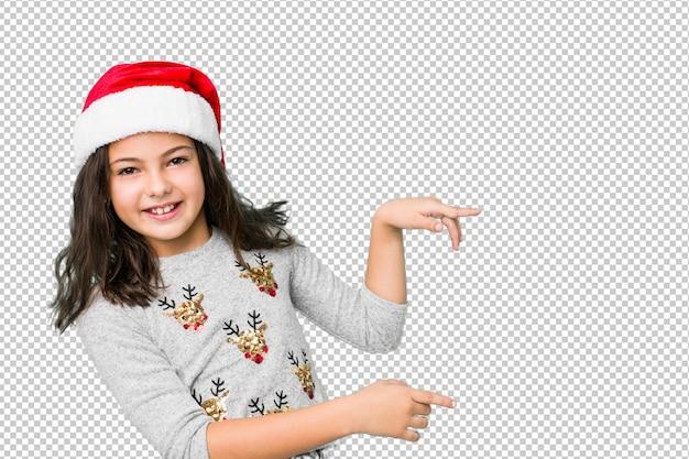 クリスマスの日を祝う少女は、人差し指で離れて指している興奮しています。