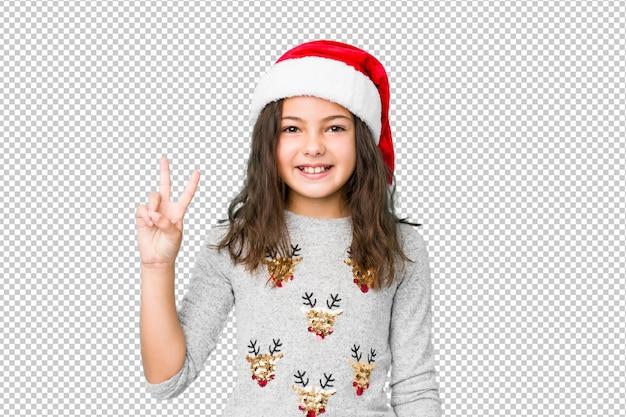 勝利のサインを示し、広く笑顔のクリスマスの日を祝う少女。