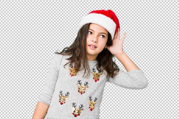 ゴシップを聴こうとしてクリスマスの日を祝っている少女。