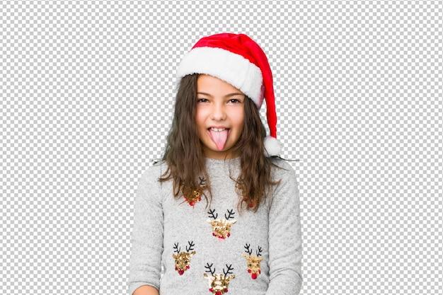 面白いとフレンドリーな舌を突き出てクリスマスの日を祝う少女。