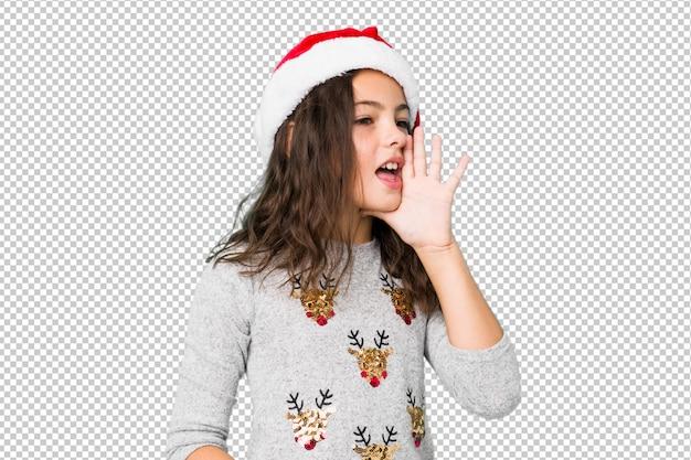 クリスマスの日を祝って、開いた口の近くの手のひらを保持している小さな女の子。