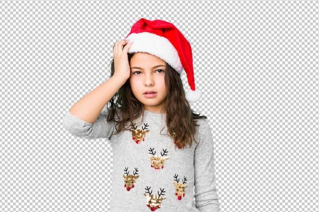 クリスマスの日を祝っている女の子が疲れて非常に眠くて頭を握っています。