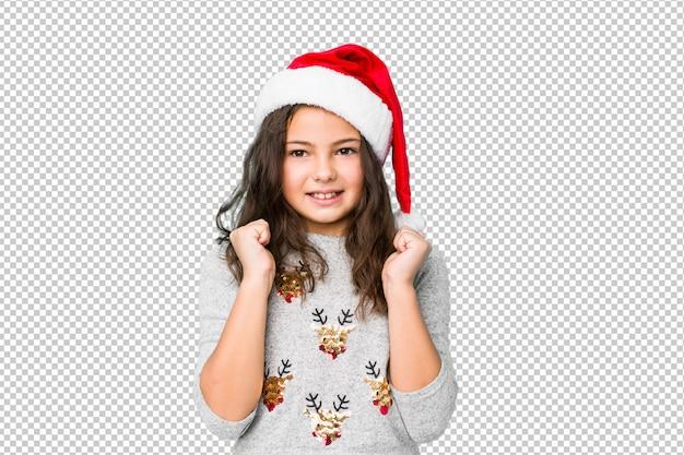 Маленькая девочка празднует рождество, поднимая кулак, чувствуя себя счастливым и успешным. концепция победы.