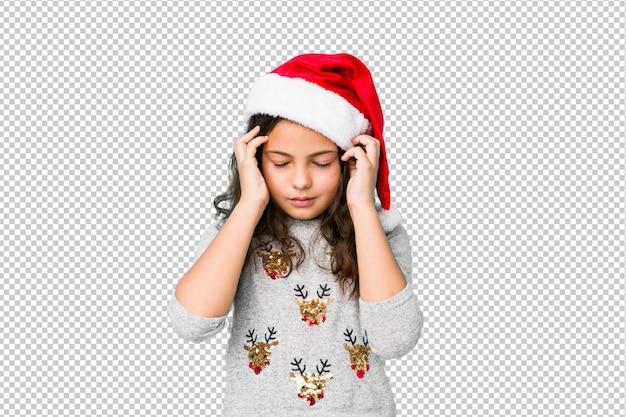 Маленькая девочка празднуя виски рождества касающие и имея головную боль.