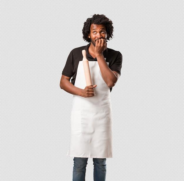 Красивый афроамериканский пекарь кусает ногти, нервничает и очень переживает и боится будущего, испытывает панику и стресс